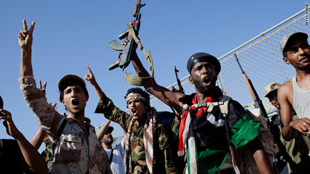 Libyan rebel fighters celebrate as they arrive in Tripoli on an ex-Libyan Army frigate on Tuesday.