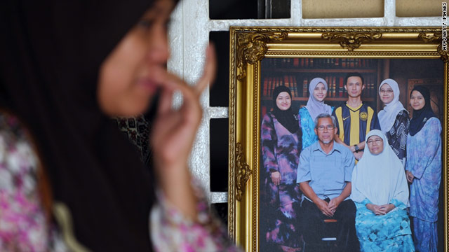A relative of Bernama TV journalist Noramfaizul Mohd Nor mourns next to a group family photo showing the cameraman.