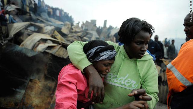 A woman is comforted after seeing the body of her child on at the scene of a fire in a slum area in Nairobi.