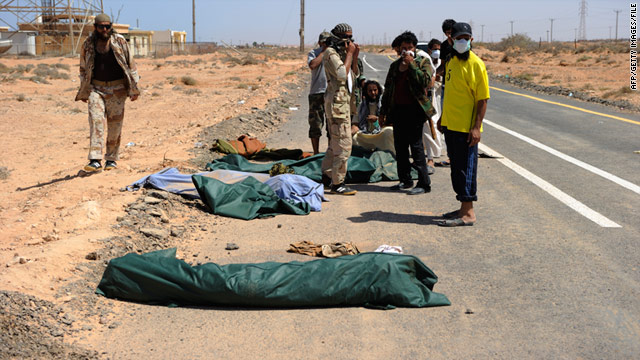 NTC fighters look at one of the four bodies they found buried on September 03, 2011 near Bir Umm al-Khanafis.
