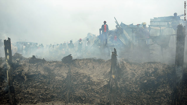 Residents of the Nairobi slum stand among smouldering debris following the fierce fire.