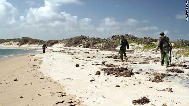 Armed policemen patrol a stretch of beach near Kiwayu Safari village, Kenya, on September 12, 2011.