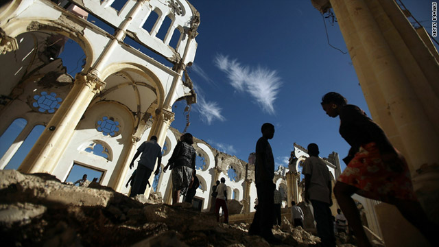 Haitians walk through the destroyed Port-au-Prince cathedral during services outside on Wednesday.