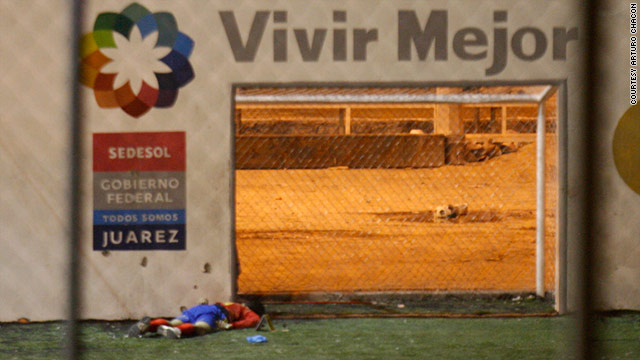 "A body lies below a sign that reads ""Live Better"" in Spanish -- a slogan in Juarez's anti-violence campaign."