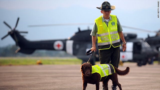 A Colombian police officer with a police dog stands guard next to two Brazilian helicopters with the Red Cross colors at the airport of Florencia, department of Caqueta, Colombia, on Thursday.