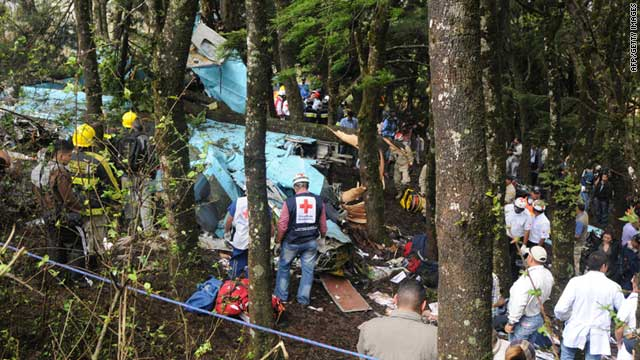 Members of the Red Cross, the Fire Department and other officials search for victims among the wreckage of the plane.