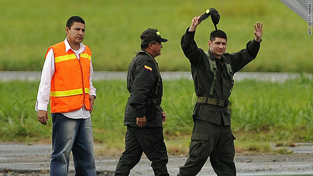 Released hostage Police Maj. Guillermo Solorzano waves Wednesday before boarding a plane for Bogota.