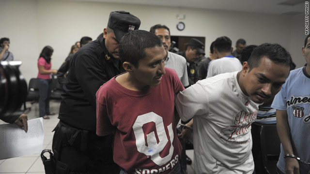 An officer handcuffs two of the eleven Salvadoran gang members convicted in the killing of filmmaker Christian Poveda.
