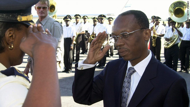 On January 12, 2004, then-President Jean Bertrand Aristide is saluted by a police officer before his departure from Haiti to Mexico to attend a summit. Just weeks later, he fled Haiti and went into exile.