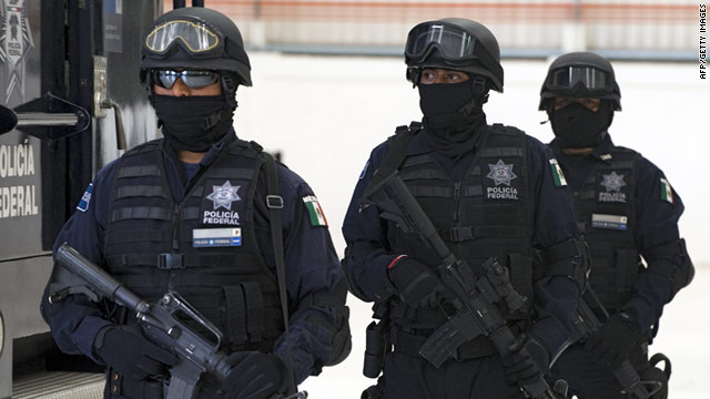 Mexican police stand guard in front to the truck where Marcos Carmona Hernandez -- alleged leader of the Oxaca state Zetas drug trafficking gang -- was transported to be presented to the press in Mexico City on March 7, 2011.