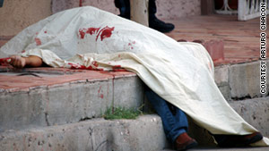 A victim of one of Juarez, Mexico's, 41 recent murders lies covered in the street.