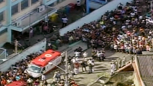 People stand outside a school in Rio de Janeiro where children and adults were reportedly shot to death on Thursday