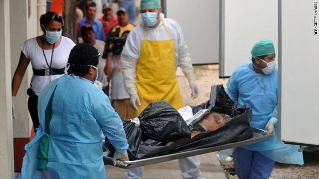 Forensic workers move one of the bodies found in a northern border province of Guatemala on May 15.