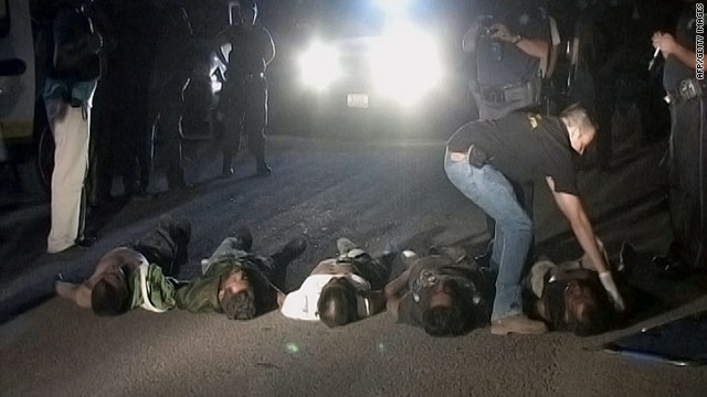 A state police officer checks bodies found near Morelia, Mexico, on Wednesday night.