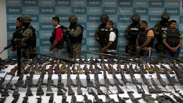 Mexican officers escort five alleged drug traffickers of the Zetas drug cartel in front of the press in Mexico City on June 9.