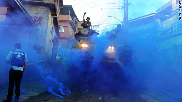 A member of the military throws a blue smoke flare in Rio de Janeiro, where authorities seized 300 packs of marijuana Sunday.
