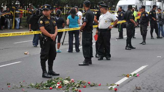 Police stand near roses laid at the scene of Saturday's shooting of Argentine folk singer Facundo Cabral in Guatemala City.