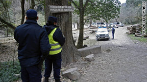 Police officers on Saturday stand at the entrance to a hiking trail where two French tourists were killed in Salta, Argentina.