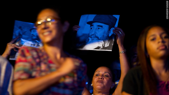 Cubans hold up pictures of former Cuban president Fidel Castro during a concert on August 13 at the Karl Marx theater in Havana.