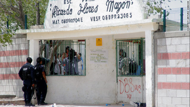 Police stand outside an elementary school in Mexico, where unknown gunman open fired on a crowd.