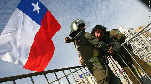 A demonstrator waving a Chilean flag is arrested by riot police officers in Santiago on August 25.