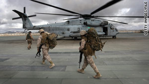 Marines head to a transport helicopter in Afghanistan. More Marines will be posted in the south, an official says.