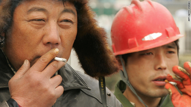 Two men smoke cigarettes on a street in Beijing. Over 300 million people in China are regular smokers, most of them men.