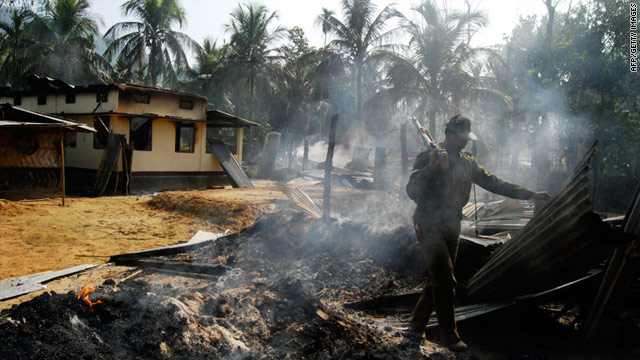 A security official inspects a house burned during an upsurge of violence between rival ethnic groups in northeast India.