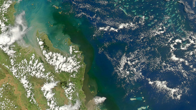 The flood water plume (brown color), as seen from a satellite, emerging from the mouth of the Fitzroy River (bottom of pic) and spreading north and towards coral reefs, on January 4 2011.