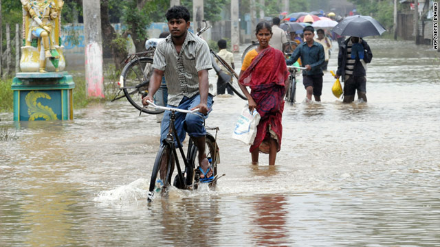 Sri Lankan people walk on a flooded road of the eastern Sri Lankan town of Batticaloa on January 14, 2011.