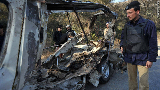 A Pakistani policeman stands near the wreckage of a passenger van after a bomb blast in Jawarza, near Hangu.