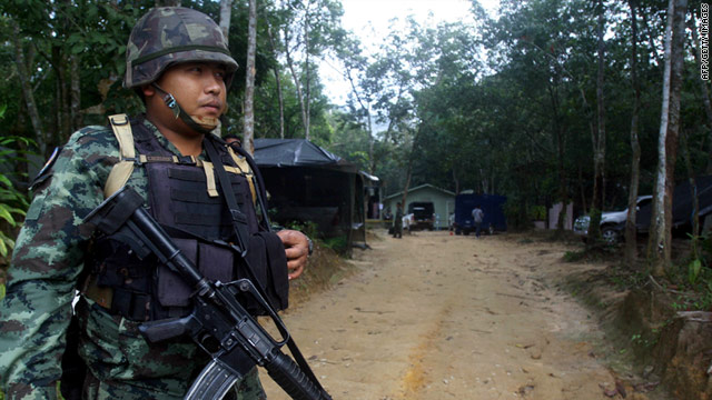 A Thai soldier guards the entrance to a military camp following a raid on the camp by armed rebels in Narathiwart province.