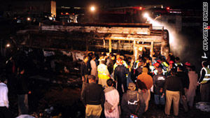 Pakistani officials gather beside the wreckage of a burnt out bus after it collided with an oil tanker.