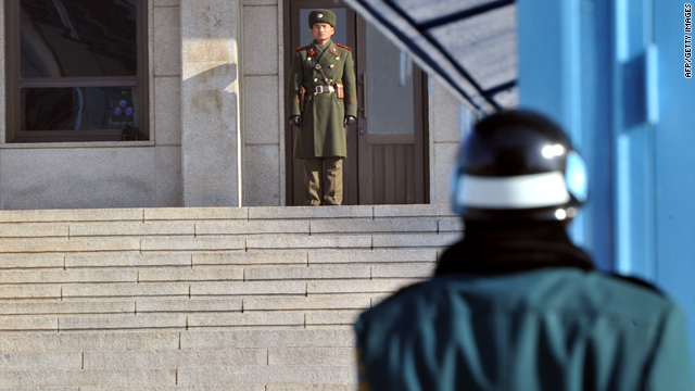 A North Korean soldier, center, and a South Korean soldier stand guard at the truce village of Panmunjom in the Demilitarized Zone separating the two Koreas on January 19, 2011.