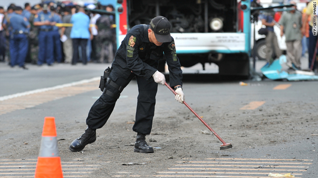 A Philippine police investigator looks for evidence next to a bus where a bomb exploded inside along the main avenue in the financial district of Manila on Tuesday.