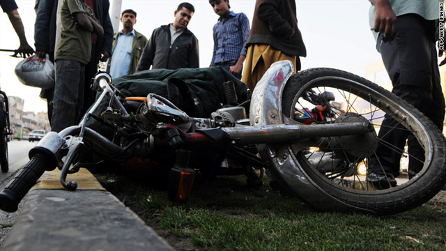 Onlookers examine the motorbike of two boys who were allegedly shot and killed as they tried to rob a U.S. official in Lahore.
