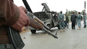 Afghan police inspect the wreckage of the deputy governor's car Saturday after an attack by a suicide bomber in Kandahar.