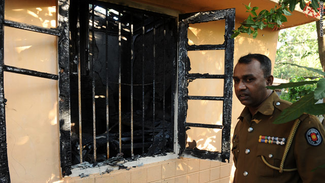 A Sri Lankan police officer examines the torched office of Lanka-e-News, a website critical of the government.