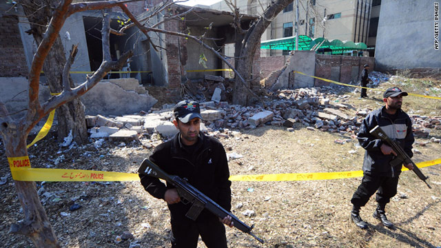Police stand guard after a bomb blast behind the police building in Gujranwala, near Lahore on February 9, 2011.