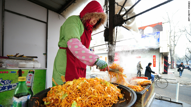 A vendor pan-fry's noodles from her stall, selling them for eight yuan ($1.21) per order in Beijing on Wednesday.