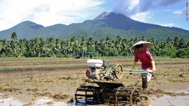 A farmer prepares his farm for planting rice in San Juan village in Sorsogon province under the restive Mount Bulusan volcano seen in the background, 21 June 2006.