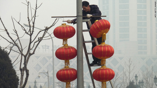 Workers remove red lantern decorations for the just completed lunar festivities amid stifling smog in Beijing Wednesday.