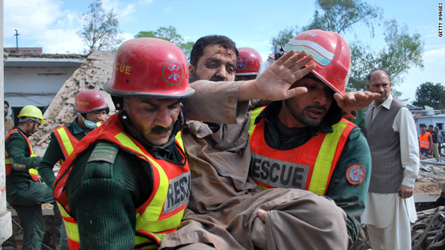Rescuers pull people to safety after a bomb blast at a gas station in Pakistan killed 21 people and injured many others