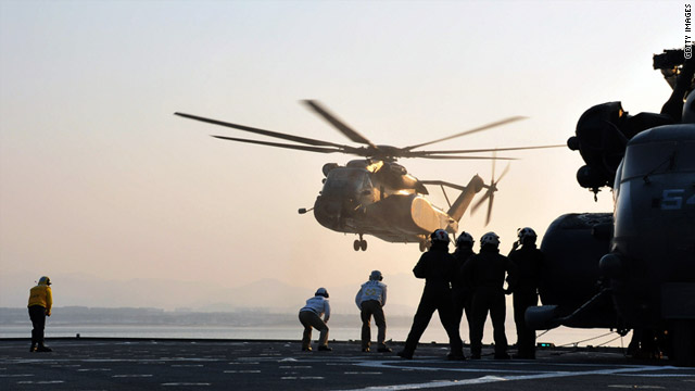 Helicopters land on the USS Tortuga in the Sea of Japan on Saturday as the U.S. military prepares to deliver aid.