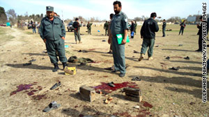 Security personnel look over the site of a suicide bomb attack in Kunduz, Afghanistan.