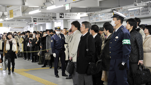 Commuters wait on a Tokyo subway platform on Monday. Services were only running at about 20 percent.