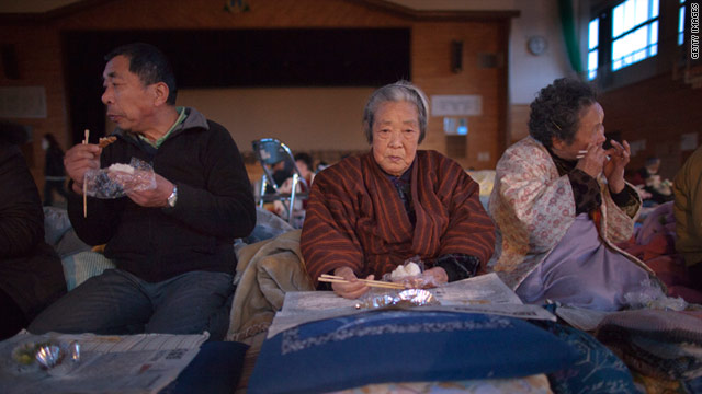 Japanese families eat dinner at a shelter on March 16, 2011 in Kesennuma, located in the northeast of Miyagi prefecture.