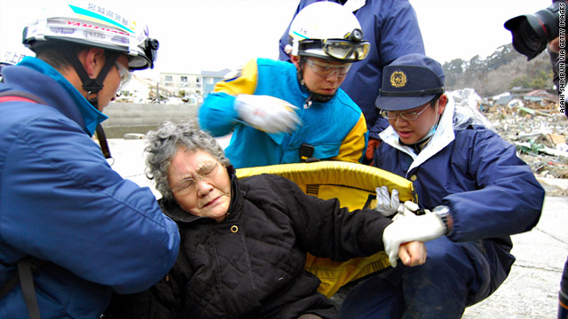 Rescuers help an 80-year-old woman who had been trapped in her home along with her grandson.