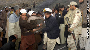 Pakistani miners and their relatives carry the dead body of a miner from a coal mine in Sorange district.