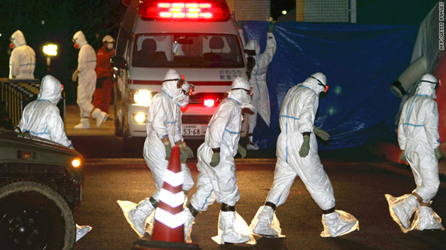 Workers in protective suits prepare Thursday to decontaminate two nuclear plant workers in Fukushima, Japan.